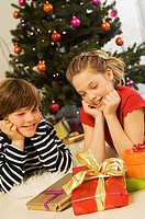 Close-up of a brother and his sister looking at Christmas presents
