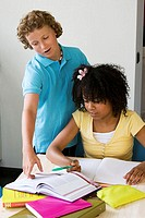Girl doing her homework with a boy standing near her