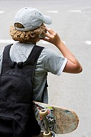 Rear view of a boy using a mobile phone
