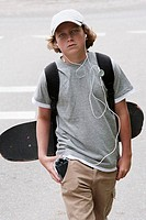 Close-up of a boy carrying a skateboard and a backpack