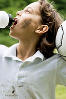 Close-up of a boy holding a soccer ball and drinking water