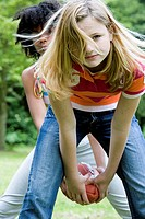 Portrait of two girls playing with a football
