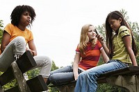 Low angle view of three girls sitting on benches