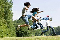 Side profile of four children jumping in a park