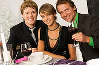 Portrait of a young woman smiling with two mid adult men at a dining table