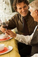 Close-up of a senior man and his son toasting with wineglasses