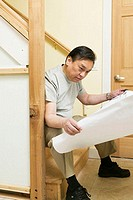 Side profile of a mid adult man sitting on steps and looking at a blueprint (thumbnail)