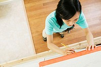 High angle view of a young woman using spirit level to mark on a wall