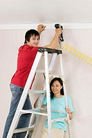 Portrait of a young man using a drill on a wall with a young woman holding a ladder (thumbnail)