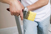 Mid section view of a man holding a paintbrush
