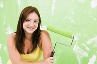 Portrait of a young woman holding a paint roller