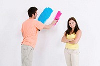 Young man painting a wall with a young woman standing beside him