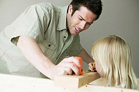 Father holding a tape measure with his daughter marking on a plank with a pencil