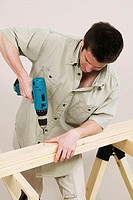 Close-up of a young man drilling into a plank