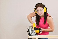 Portrait of a young woman cutting wood with an electric saw