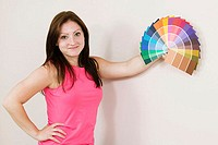 Portrait of a young woman holding color swatches