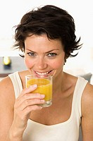 Portrait of a young woman drinking orange juice