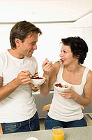 Close-up of a young couple holding bowls of fruit salad and smiling (thumbnail)