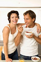 Portrait of a young woman smiling with a young man eating fruit salad beside her