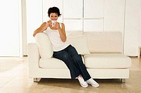 Young woman sitting on a couch with a cup