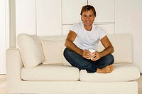 Portrait of a young man sitting on a couch and smiling (thumbnail)
