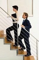 Side profile of a businesswoman climbing up stairs with a businessman