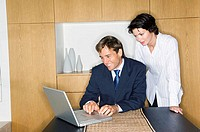 Businessman using a laptop with a businesswoman standing beside him