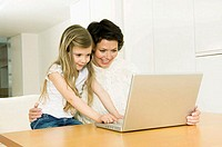 Close-up of a girl using a laptop with her mother