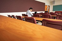 Side profile of a college student sitting in a lecture hall and using a laptop