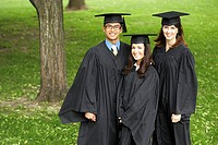Portrait of two female graduates and a male graduate smiling