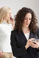 Close-up of a businesswoman using a PDA with another businesswoman talking on a mobile phone
