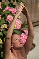 Close-up of a mature woman meditating in a tree pose