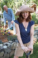 Portrait of a mature woman with a shovel and a mature man kneeling in the background