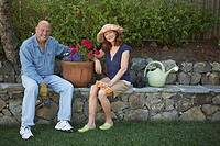 Portrait of a mature couple sitting in a garden and smiling