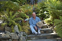 Mature man sitting on steps in a garden