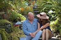 Close-up of a mature couple sitting in a garden and looking at each other