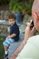 Rear view of a mature man taking a photograph of his grandson