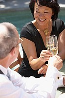 Close-up of a mature woman and a mature man toasting with champagne flutes
