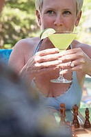 Close-up of a mature woman drinking a martini