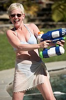 Mature woman spraying water with a squirt gun