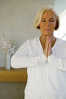 Senior woman meditating, eyes closed, close-up
