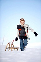 Austria, boy (12-13) pulling sledge in snow