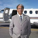 Senior Indian businessman in front of airplane, Perth, Australia