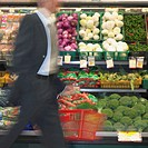 Blurry view of man walking by produce in supermarket, Perth, Australia