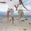 Couple jumping on the beach, Busselton, Australia