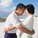Senior Asian couple hugging at the beach, Perth, Australia