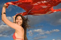 Young woman holding shawl over her head in the wind (thumbnail)