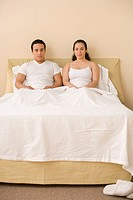 Hispanic couple sitting in bed