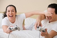 Hispanic couple lying in bed playing video games
