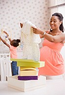 Pregnant African mother opening gifts of baby clothes